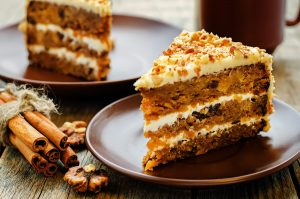 A slice of multi-layered carrot cake with cream cheese frosting between the layers. A stick if cinnamon sits in the foreground.
