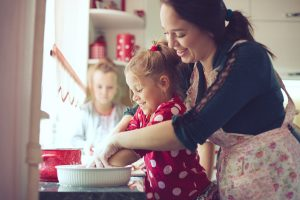 A woman leans over a small child in a kitchen, showing the child how to place the dough for pie crust in a pan. Behind them, another child watches.
