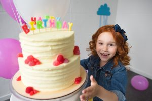 "A small girl with red hair and a denim jacket excitedly presents a tiered cake to the viewer. The cake has candles on it spelling out ""happy birthday."""