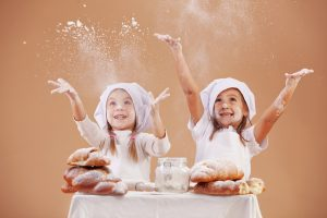 Two small children wearing chef's hats are throwing flour into the air. In front of them is a table full of materials for baking.