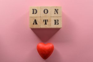 """The word """"donate"""" spelled out on wooden blocks, with a three dimensional heart beneath."""