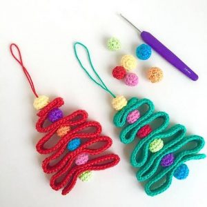Two crochet Christmas trees with hoops to be hung as ornaments. One is green and one is red. Small felted balls and a felting needle sit beside them.