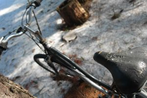 Old bike with a cracked seat and a stick stuck through the gear cables.